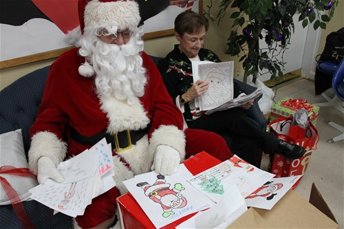 Santa II (looking a lot like one of our members) sifts through the coloring to pick a winner. It was a hard job. He is assited by Chief Elf Rita Schief.